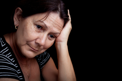 Older woman with a very sad expression isolated on black